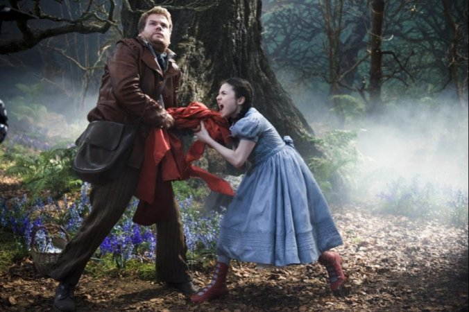 The Baker (James Corden) attempts to steak the Red Riding Hood from hers truly (Lilla Crawford). Her unbearable screaming doesn't make you root for her any more than you should.